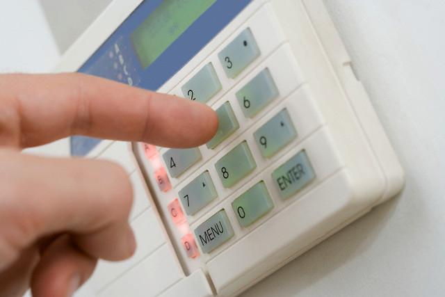 A person setting a burglar alarm